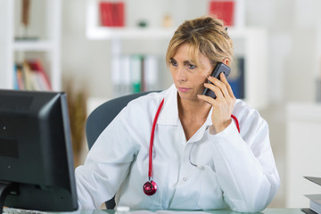 female doctor sitting at her office while phoning her patient