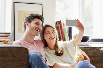 Smiling Young Couple Taking Selfie On Sofa