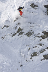 Professional snowboarder jumping a cliff in the snowy mountain in the Pyrenees