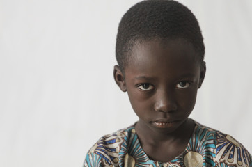 Angry young African boy isolated on white, showing his face for a portrait