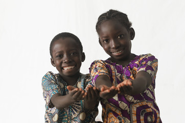 Two African children showing their palms asking begging for something, whilst smiling, isolated on white
