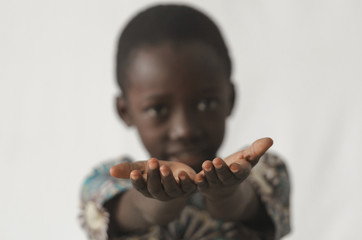 African boy holding his hands open as a concept, isolated on white and blurry background