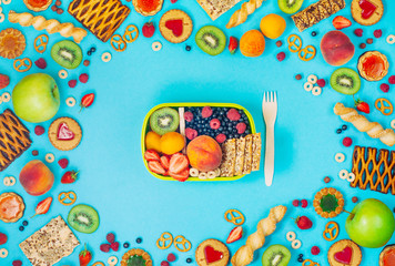 Frame with lunch box and lots of fruits, berries and crunches on blue background