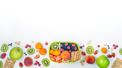 Frame with lunch box and various fruits, berries and crunches on white background