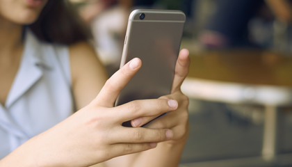 close-up of a girl taking pictures of herself on a gray phone in daylight. background blur