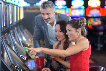 friends in casino on a slot machine