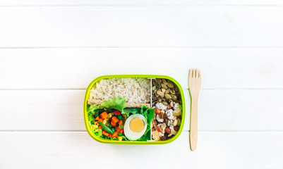 Lunch box and fork on white wooden background with copy space