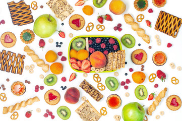 Lunch box and variety of fruits, berries and crunches on white background