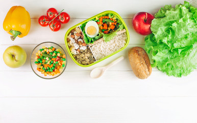 Lunch box filled with rice and mixed vegetables on white wooden background