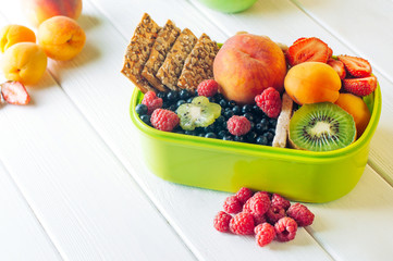 Lunch box with fruits, berries and crunches on white wooden background