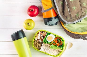 Top view of lunch box and backpack with thermos mug on light wooden background