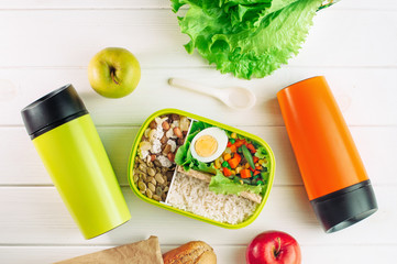 Top view of lunch box and two thermos mugs on light wooden background