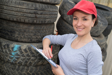 female mecanic surrounded by stacks of car tyres
