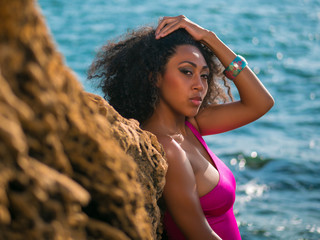 Portrait of cheerful black people, pretty happy young african american woman smiling. Rocks beach. Sexy girl in pink swimsuit and jewelry enjoying nature. Travel, holiday concept.