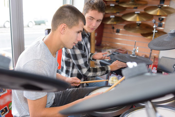friends musicians with trying drums at music store