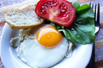 Fried egg on a plate with tomato and lettuce leaves. Selective focus. Horizontal.