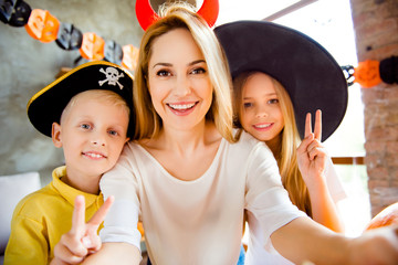Cropped close up family portrait of three at halloween party. Happy mommy and her cheerful kids - blond small witch and pirate, bonding, lady is making selfie, siblings showing like signs