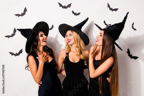 Group of three diverse charming, happy coquettes in dark masquerade elegant dresses, talking, smiling, engoying near decorated wall with bats, toothy beaming smiles scary bright cosmetics hot figures