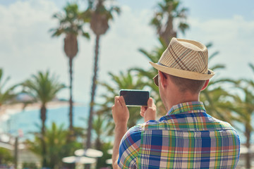 Man in sunhat making photo of amazing sea view with his smartphone.