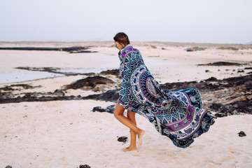 Woman walking on the beach with a towel mandala