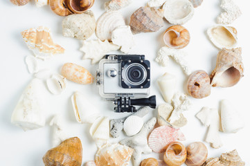 Action camera and seashells and  on a white background. The concept of memories or dreams