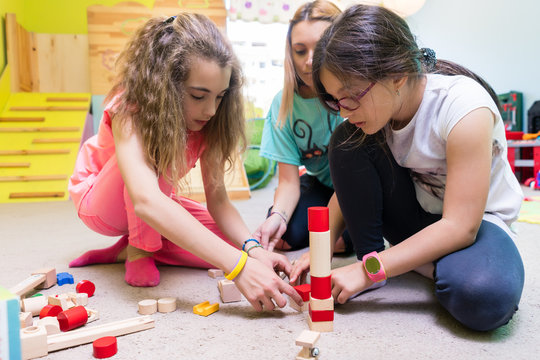 Two pre-school girls playing together with wooden toy blocks on the floor during playtime supervised by a careful young kindergarten teacher