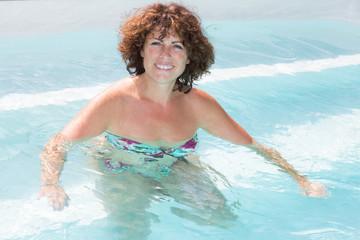 beautiful woman sitting on the edge of the swimming pool