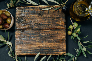 Healthy snack: Dark and green olives, oil, goat cheese on a wooden board, space for text