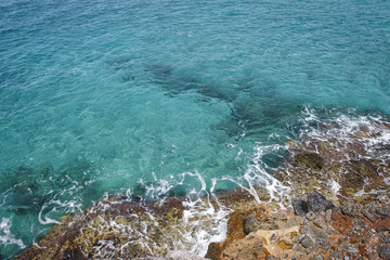 Aerial. Waves swim to the rocky shore. Aerial top view of sea waves hitting rocks on beach, Turkey