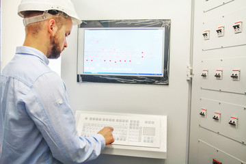 engineer controls technological equipment from remote control board. Scada system for automation equipment