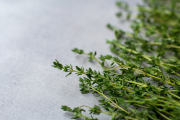 Food background: thyme herb on a grey kitchen table from right side
