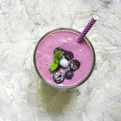 Berry smoothie in a glass with paper straw.Top view,square image.