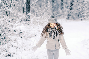 Little girl in a gray jacket with a knitted cap and scarf, toss snow in the winter forest. Children play outdoors in a snow-covered forest. Children catch snow flakes.