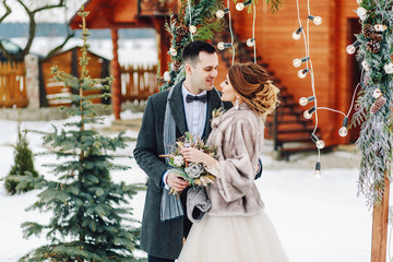 Groom tenderly embracing her beautiful bride. Winter wedding ceremony in rustic style outdoors. Happy and stylish newlyweds