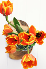 Abstract of an orange and yellow tulip bouquet arrangement in a mason jar shot from above.