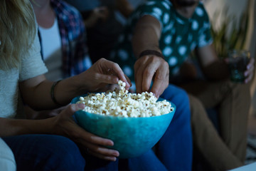 Group of friends watching tv together and eating popcorns