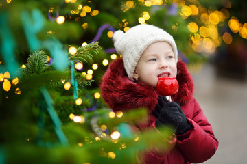 Adorable little girl eating red apple covered with sugar icing on traditional Christmas market.