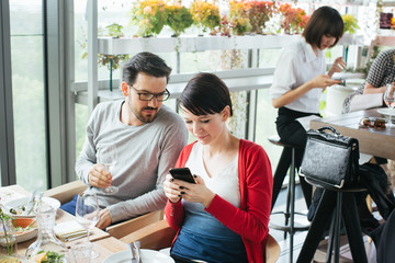 Lunch With Friends - Caucasian Woman Showing Something on Cellphone to Male Friend