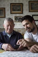 Adult grandson explaining to his granddad how to use a smartphone