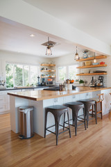 Bright modern kitchen with wood bar and open shelving