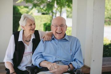 Happy, fun loving elderly couple outside in garden using wheelchair