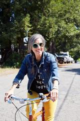 Portrait of stylish senior woman riding a bike outdoors