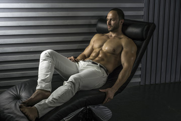 Sexy, serious and dominant young shirtless handsome muscular fitness model rests on a chair