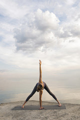 Unrecognizable girl practicing yoga against of white clouds over sea