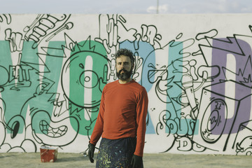 Man painting in a graffiti wall