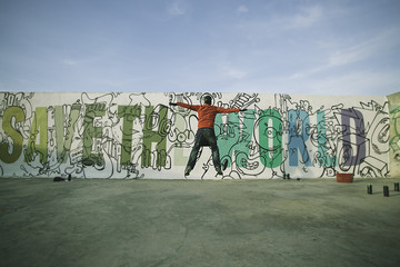 Man jumping in front of a graffiti wall