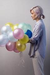 Side view of young girl holding bunch of colorful balloons