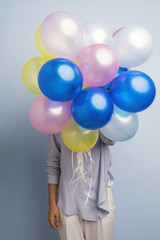 Unrecognizable girl with colorful balloons
