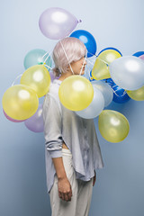 Pink-haired girl with balloons over her head