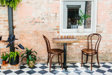 A lounge area with seating / checkered floor & vintage brick walls.